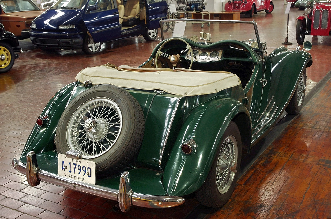 """MG TF 1500 - 1955, rear view. Lane Motor Museum, Nashville, Tennessee. From their website:<br /> <br /> """"In 1949, the MG TC gave way to the MG TD; in 1953, the MG TD gave way to the MG TF. The TF was at the time a rather unsuccessful attempt to stall the impatient car enthusiasts who had started to get tired of the long series of the T-type and were crying for something new. Hence, the TF became a short production series before the MGA was released. It was basically a cosmetic modification of the TD but had a more modern look, with a more inclined radiator and built-in head lamps. In hindsight, the TF turned out to be perhaps the most beautiful of all the MG models."""""""