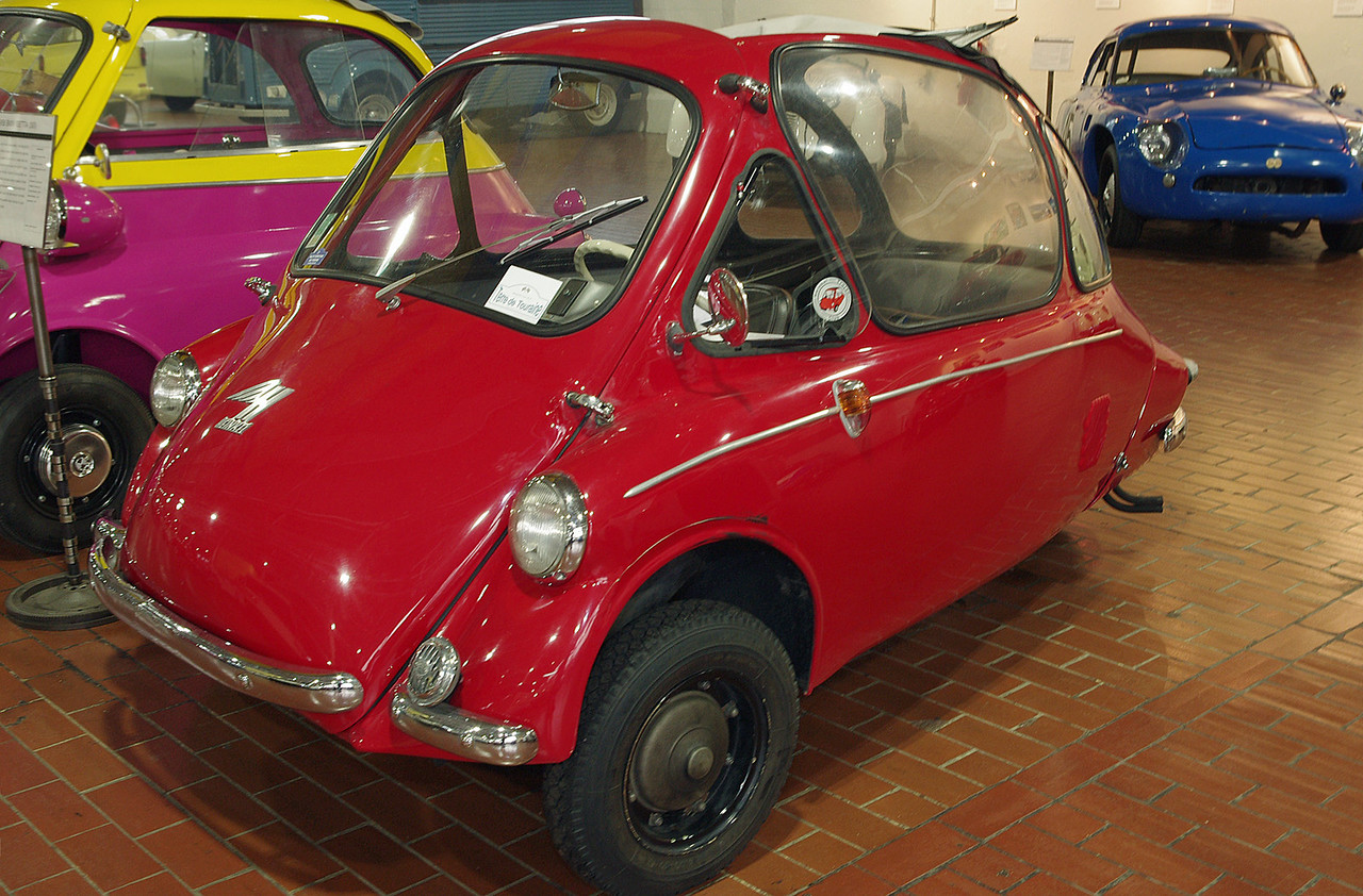 """1956 Heinkel. Lane Motor Museum, Nashville, Tennessee. <br /> <br /> Heinkel, like Messerschmitt, was prohibited from making aircraft after WW2. Heinkel started producing bubble cars in 1956. This particular car won the """"under 200 cc"""" class in the 1200 mile Microcar rally from Liege, Belgium to Brescia, Italy, and back (2008). Lane museum owner Jeff Lane drove the car, with the car's owner Claude Gueniffey navigating. After driving it flat out for 6 days and 10 hours, Jeff Lane says he was impressed with the car's engineering. Claude donated the car to the museum in 2012.<br /> <br /> Heinkel stopped production in 1958, but sold the license to Trojan in Ireland where they were made until 1965."""