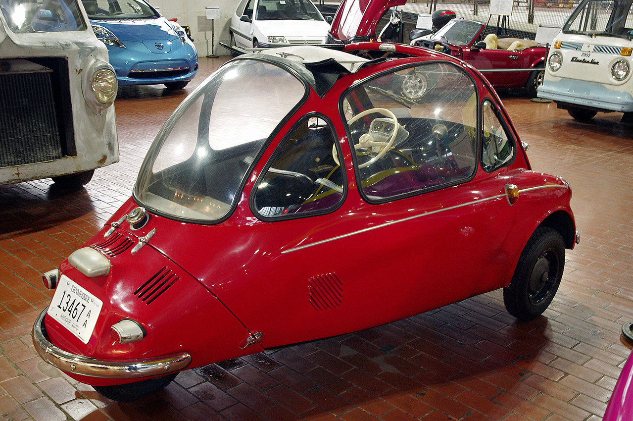 """1956 Heinkel. Lane Motor Museum, Nashville, Tennessee. <br /> <br /> Heinkel, like Messerschmitt, was prohibited from making aircraft after WW2. Heinkel started producing bubble cars in 1956. This particular car won the """"under 200 cc"""" class in a 1200 mile Microcar rally from Liege, Belgium to Brescia, Italy, and back (2008). Lane museum owner Jeff Lane drove the car, with the car's owner Claude Gueniffey navigating. After driving it flat out for 6 days and 10 hours, Jeff Lane says he was impressed with the car's engineering. Claude donated the car to the museum in 2012.<br /> <br /> Heinkel stopped production in 1958, but sold the license to Trojan in Ireland where they were made until 1965."""