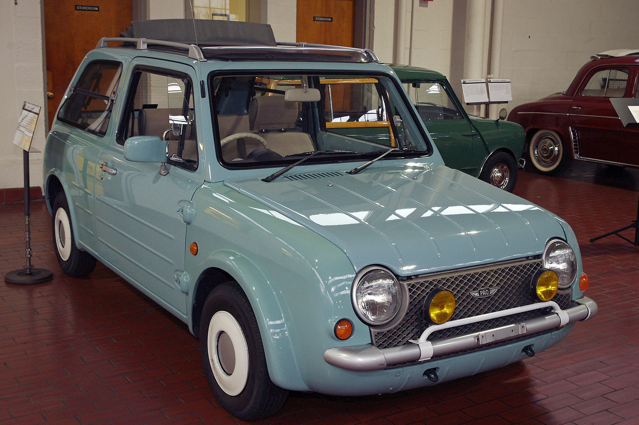 """Nissan Pao; Lane Motor Museum, Nashville, Tennessee.<br /> <br /> From Wikipedia:<br /> The Pao was sold without the Nissan name and only by reservation from January 15 through April 14, 1989. The Pao sold out in 3 months and remains a sought after and collectible car, with only about 51,657 made.<br /> <br /> Part of Nissan's """"Pike"""" series, it was designed as a retro fashionable city car. It included external door hinges like the original 1960s Austin Mini which had become fashionable in Japan, 'flap-up' windows like those of a Citroën 2CV, and a split rear tailgate of the first British hatchback car the Austin A40 Farina Countryman."""