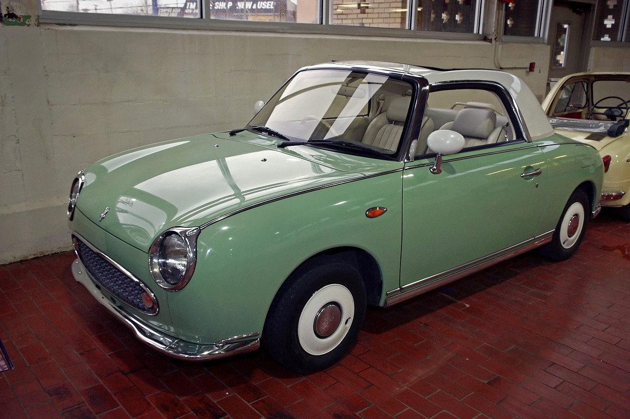 1989 Nissan Figaro; Lane Motor Museum, Nashville, Tennessee.<br /> <br /> From wikipedia:<br /> Built by a Nissan special projects group called Pike Factory (which was not really a factory - more of a design group). The Figaro, which was sold without the Nissan name, was designed by Shoji Takahashi, who won a design competition with the car. Only 8000 were originally available with an additional 12,000 added to production numbers to meet demand. Prospective purchasers had to enter a lottery to be able to buy one of these cars.