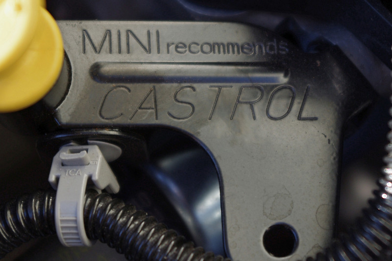"On the phone MINI says only MINI brand oil should be used for an oil change - but this little message - ""MINI recommends Castrol"" - appears in the Owner's Manual, and again here, under my hood next to the dipstick. <br /> <br /> Now it's no great secret that Castrol makes MINI brand oil - so I thought I might save myself a 3.5 hour drive to the dealership and just substitute whatever oil Castrol recommends for my car.<br /> <br /> Except Castrol's website says they have NO RECOMMENDATIOS for my MINI (I confirmed this with two tech people at Castrol). That's right, MINI recommends Castrol - but Castrol recommends nothing in their US product line for the MINI. Nada, zip.<br /> <br /> Curious and curiouser.<br /> <br /> After a few hours slogging through the posts at NorthAmericanMotoring.com and MINI2.com it appears that Castrol's product lines are different in the US and the UK. Apparently, MINI owners in the UK have access to Castrol products which are not available in the US. It's even more confusing, because Castrol's names like ""Syntec"" and ""Edge"" mean different things in different countries. When someone posts on MINI2 (a British site) that you want to use Castrol Edge, don't assume the bottle of Edge on the shelves of your American auto parts store is the same stuff."