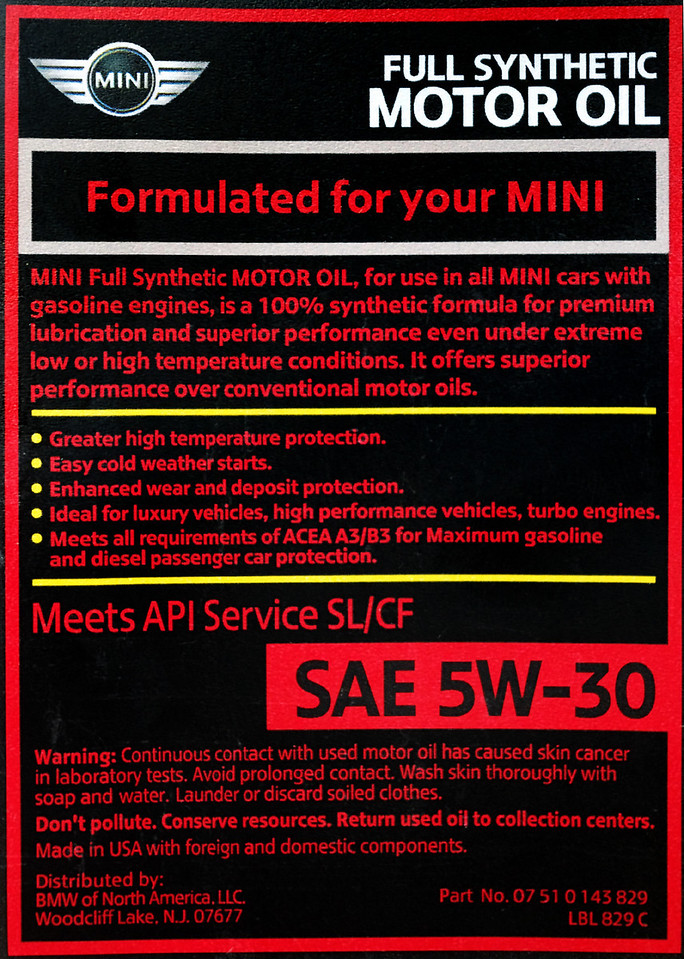 "MINI motor oil, part # 07 51 0 143 829, back label.<br /> <br /> Notice the back label for the 5W-30 says: ""Made in USA with foreign and domestic components."" It's commonly thought that this product is actually made by Castrol.<br /> <br /> Also notice: ""Meets API Service SL/CF"" - now that's odd. Remember, both the Owner's Manual and the MINI USA website says to use API SM or higher. This API SL oil meets the older specification, the one before SM - so the MINI brand oil does not meet MINI's recommended specifications!?! Does that make any kind of sense?<br /> <br /> ""Meets all requirements for ACEA A3/B3..."" That's good to know, but it's odd that neither the MINI owner's manual nor their website mentions ACEA. <br /> <br /> It's also odd that ""LL-01"" is not mentioned. That specification, which the MINI USA website says is a requirement, is a BMW specification. Seems like they would mention it if this oil meets their own spec.<br /> <br /> Anyway, I decided it's easier to go with the factory oil than it is to pick a substitute. I changed the oil and filter today (3/11/11) at 5145 miles - which should keep me and the MINI happy until my first dealer service. <br /> <br /> Changing the oil and filter is easy enough to do-it-yourself if you're not afraid to get your hands dirty. in fact I've never had a vehicle that made it any easier to get at the filter and drain plug. You'll need an 8 mm allen wrench for the drain plug, and the filter wants a 27 mm socket, but a 1 1/16"" socket works just as well. And a torque wrench, if you don't trust your instincts.<br /> <br /> Oh yeah - another bit of information you won't find in your owner's manual is the crankcase capacity - 4.5 quarts is pretty close."