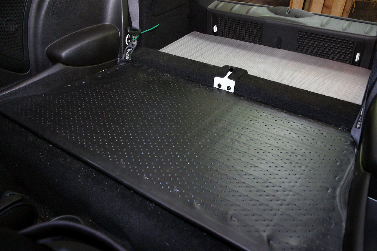 Here is my finished DIY rear seat delete.<br /> <br /> I covered the plywood with cheap a vinyl floor mat from WalMart - mounted up-side-down, so the nubbins would provide a grippier surface. I used staples around the edges, which look hideous - and did not really hold down the edges, either, so I had to use vinyl floor adhesive around the edges. Would have been better to forget about the staples, and go with the floor adhesive, only.<br /> <br /> The platform can be lifted up to access the small space beneath. I plan to keep jumper cables and a few emergency tools there - well padded to prevent rattles.