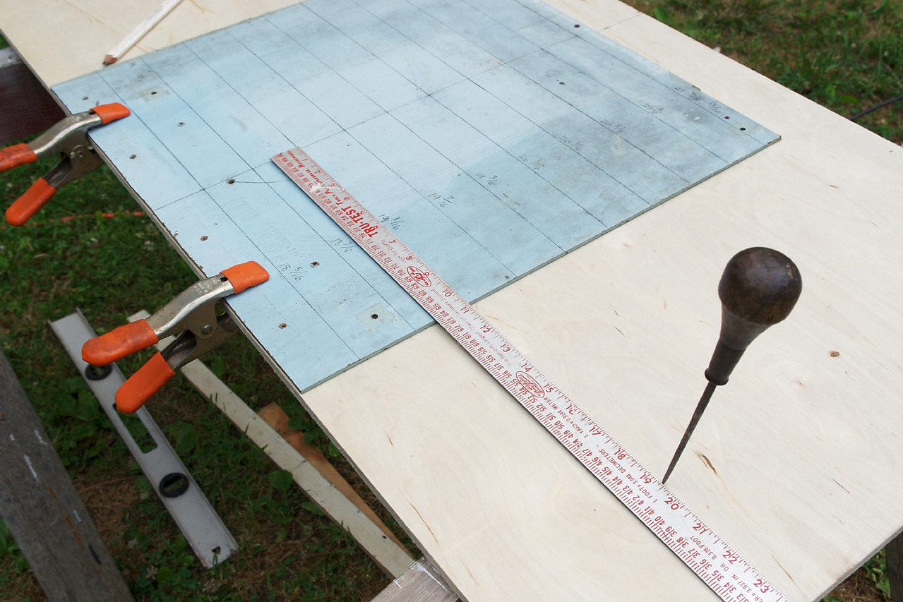 Align the centerline of the measuring panel with the centerline of the plywood platform, and mark off you measurements.<br /> <br /> Here, I'm marking directly on the plywood, but I decided to layout my shape on a piece of cardboard first. That way I was able to check the fit and make minor adjustments before cutting into the Baltic birch.<br /> <br /> Connect the dots on the cardboard template and cut the side curves. Test fit the cardboard pattern, and when you're satisfied with the fit, transfer the outline to the plywood.<br /> <br /> Cut to the inside of your line with a saber (jig) saw. Don't try to get the fit too close - it's better to cut a little small and leave a gap, than to be forced to keep whittling it down because you cut it too big.