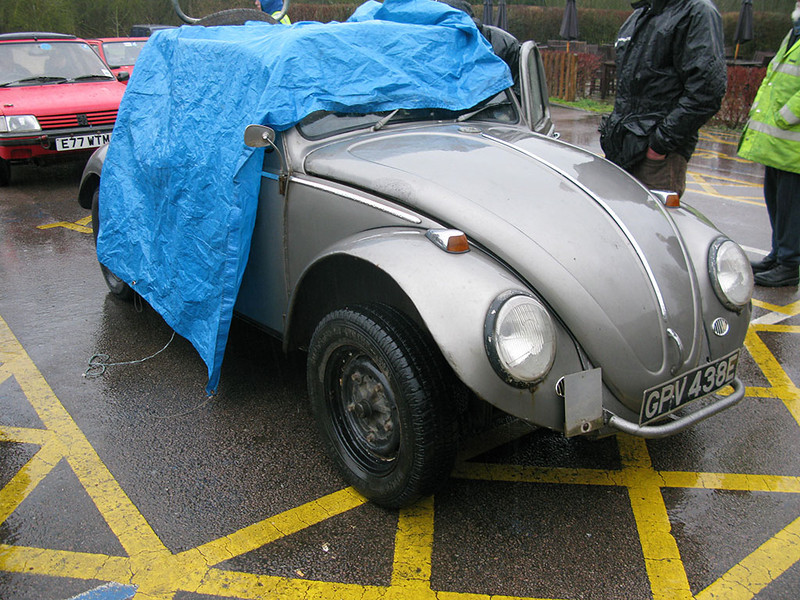 Peter Morley tries to keep his open Beetle dry