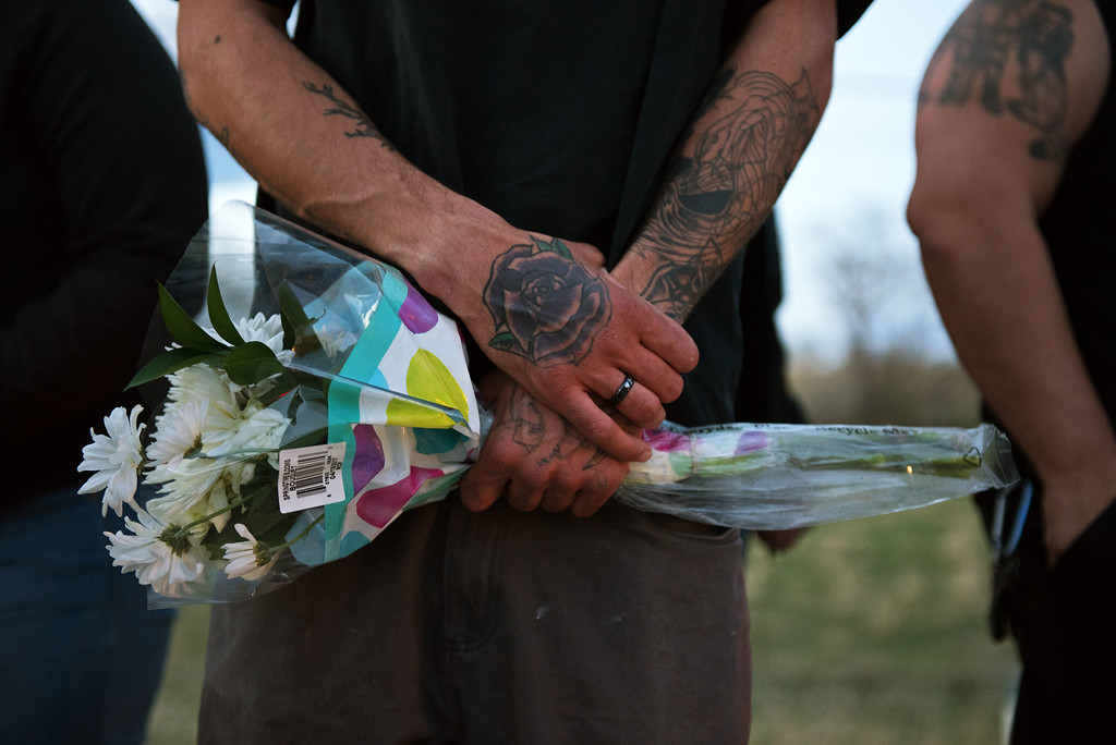 . N0419CYCLE6 Jon Giusti hold flowers during the ceremony on Monday evening April 18th, 2017, to erect a memorial for Grayson Wolff at the site where Wolff died in a motorcycle crash on highway 66 near Lyons on Sunday.  Photo by: Jonathan Castner