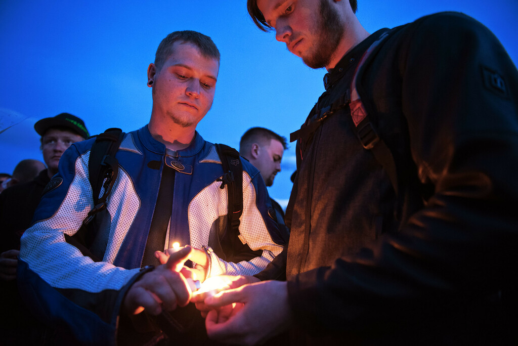. N0419CYCLE1 L-R: Chad Benallo of Longmont lights a candle for Sean Sweeney of Fort Collins during the ceremony on Monday evening April 18th, 2017, to erect a memorial for Grayson Wolff at the site where Wolff died in a motorcycle crash on highway 66 near Lyons on Sunday.  Photo by: Jonathan Castner