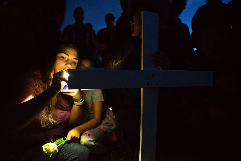 . N0419CYCLE4 Haley Sears and her daughter Karly Moncallo, age 8, both from Longmont, sign their names on the cross placed in honor of Grayson Wolff  on Monday evening April 18th, 2017. Wolff died in a motorcycle crash on highway 66 near Lyons on Sunday.  Photo by: Jonathan Castner