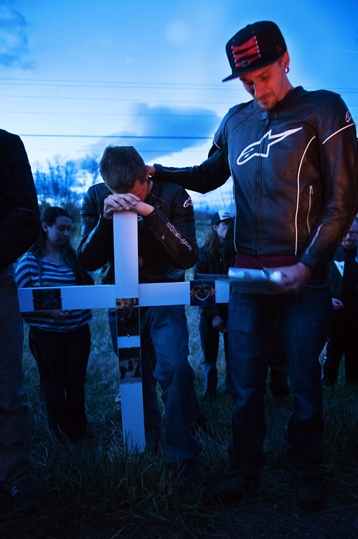 . N0419CYCLE2 L-R: Cori Thurman of Lomgmont and Dylan Oakes of Longmont hold back tears during the ceremony on Monday evening April 18th, 2017, to erect a memorial for Grayson Wolff at the site where Wolff died in a motorcycle crash on highway 66 near Lyons on Sunday. Both were friends of Wolff and were present when the crash happened.  Photo by: Jonathan Castner