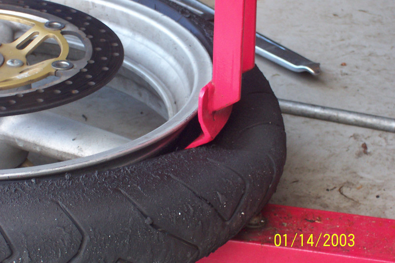 Note:  Do not push down so hard you deform the tire as this makes it harder to get off the rim.  Use just enough force to push it below the small lip on the inside of the rim.