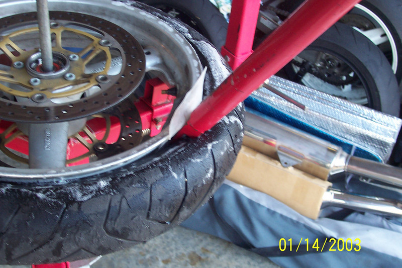 Starting in the 2:00 position, insert the red tire iron with the flat part against the rim.  Put your rim protector between the rim and the tool.<br /> <br /> (Sometimes the smaller tire iron is needed to get hold of the lip of the tire in order to get a hold of it with the larger red one).