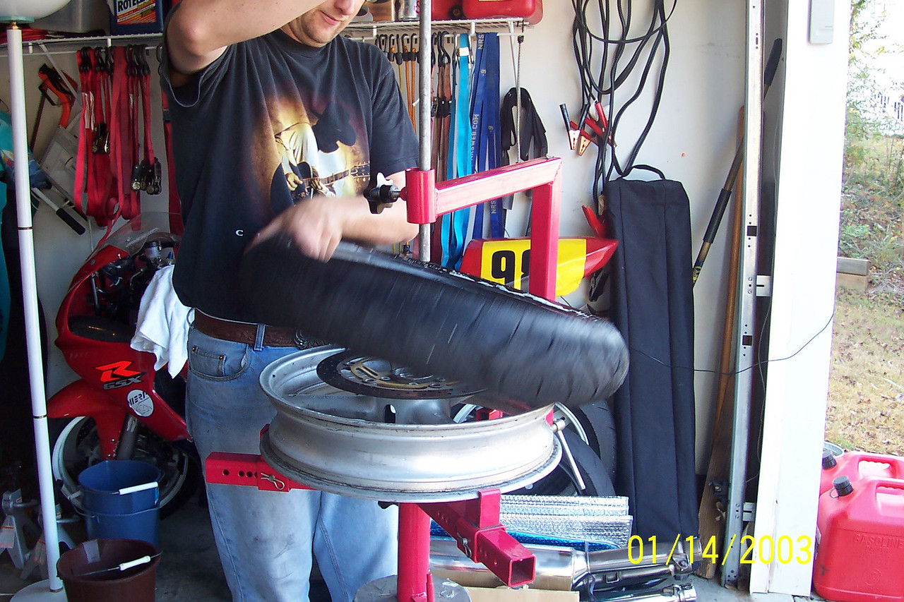 Loosen the clamps to release pressure on the rod and remove it.  Then lift the tire off.  Put new tire on and re-install the rod and re-tighten the clamps.  Again, make note of the tire direction and get it correct!  Double and Triple check this as it sucks to have to do this twice!