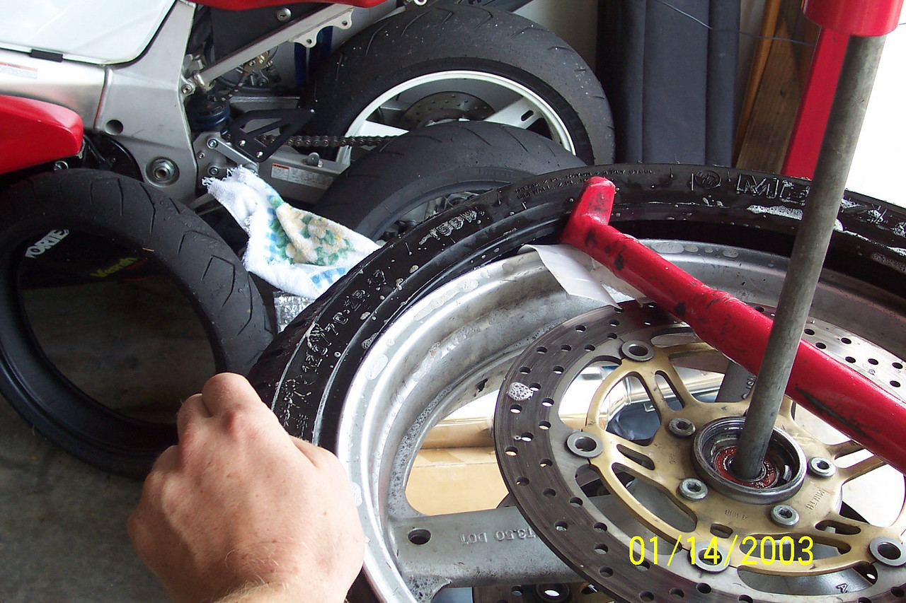 Have your assitant carefully push the bead down over the rim starting at 6:00 position and carefully work their way towards the tool as you mount the tire in a clockwise fashion. (Becareful that your assistant does not to pull the bead off the back of the tool.  If you do, start over).