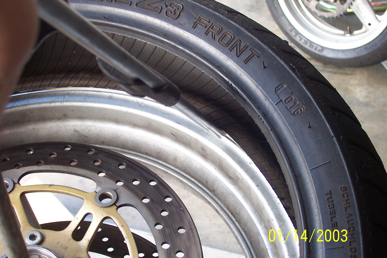 Apply pressure to pop the rest of the bead onto the rim. (Note: Don't try to force too much tire over at once.  If it's too hard, grab less tire. You don't want to break a bead here or bend a rim).