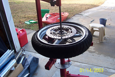 Next, remove the rim from the stand, re-install the valve stem, and add air.  You should get two good pops as the bead seats on the rim.  (Watch your fingers). If you do this right away when the tire/rim is still wet from the soapy water, it's easier.