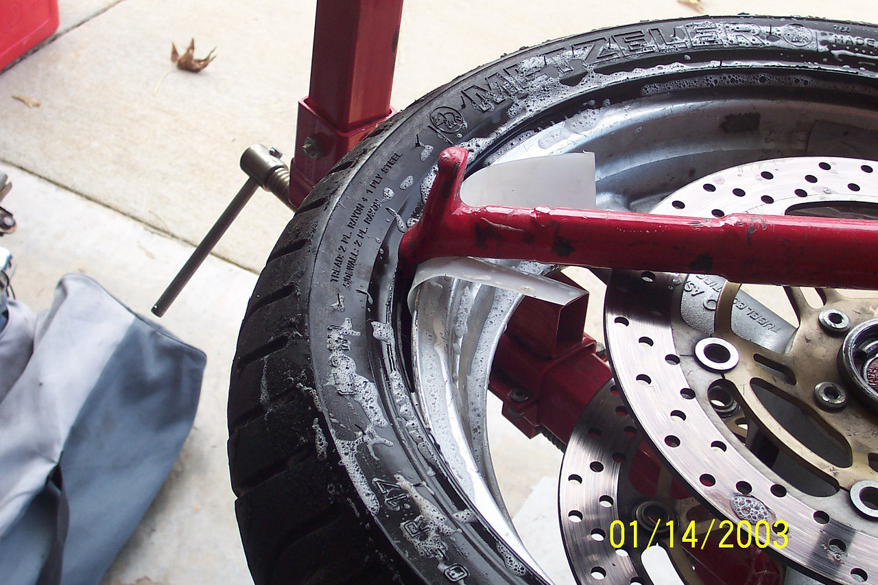 Place the tool between the metal rod and the back of the tire changer. Using the curved end, slide it over the lip of the rim where you held the tire down in the 8:00 position.  Make sure to use the rim protector.