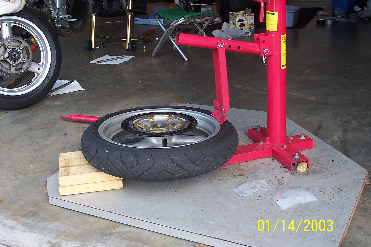 Support the other side of the tire with your wood block to keep from damaging your rotors.