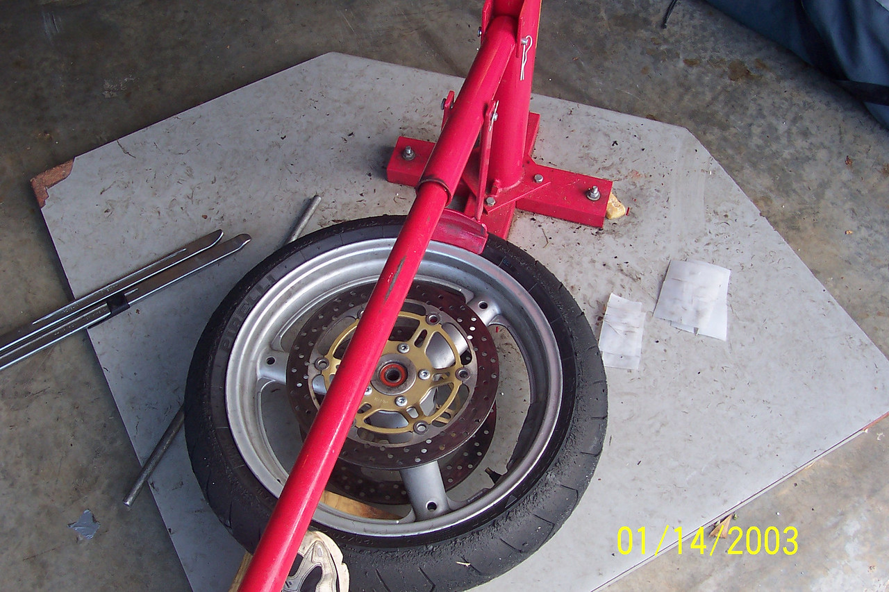Place the bead breaker at the edge of the tire and using the long bar, apply force to break the bead.  Use your foot to keep the tire from moving.