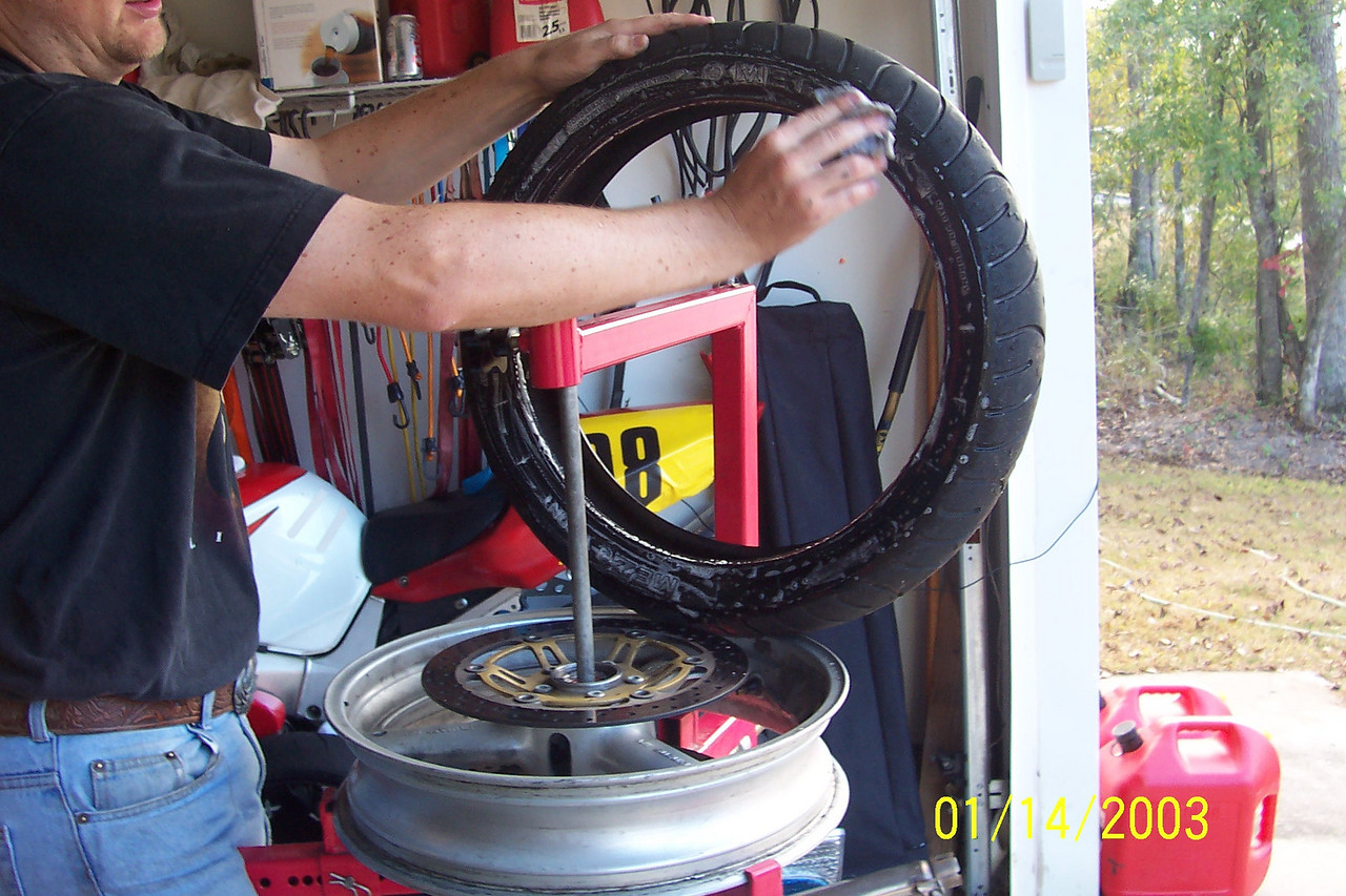 """Your new tire should have a """"paint"""" spot of some sort that marks the light spot of the tire.  Since the valve stem is the usually the heaviest spot of the rim, align that with your valve stem.<br /> <br /> A trick is to actually balance just your rim without a tire on it and mark the heavy spot.  Always align the paint spot with that and you probably won't need wheel weights.<br /> <br /> Add generous amounts of soapy water to the underside of the tire."""