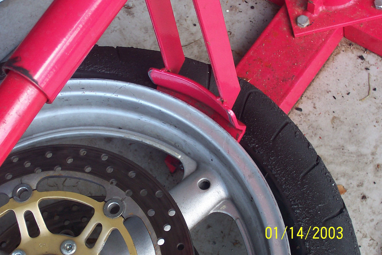 Once you break the initial bead, just work your way around the tire easily pushing the rest of the tire off the rim.  Flip the tire over and repeat until the bead is broken completely on both sides.