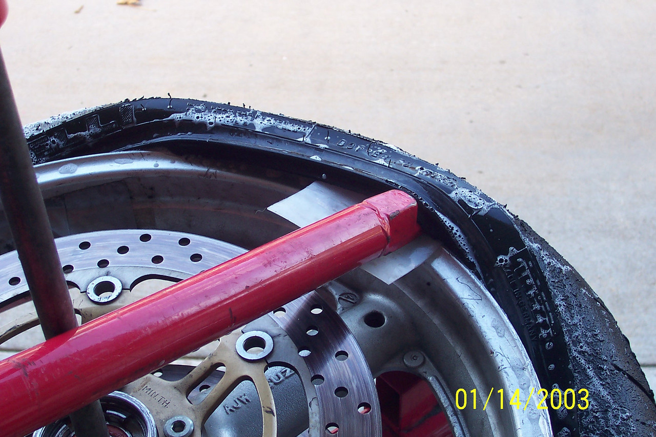 Have your partner or use your free hand to apply some pressure on the tire underneath pullying up.  Using the metal rod in the center as a brace for leverage, work the tire off the rim in clock wise fashion.  (Be very careful not to put pressure on your rotors).
