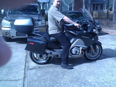 "Just for comparison, this is my son Dan who is 6'4"" with a 34"" inseam.  Although the seat does appear to be much more suited to someone his height, he can't even flat foot this seat in the natural position of just putting your feet down. He has put the majority of the miles on this seat to break it in hoping it would work better for me, but I just still can't make it work at this height.  His main complaint is that even at his height, his legs get pushed into the front fairing when trying to get them on the ground.  I'd be happy if I could get a bug chunk of my foot down like he is showing in the pics."