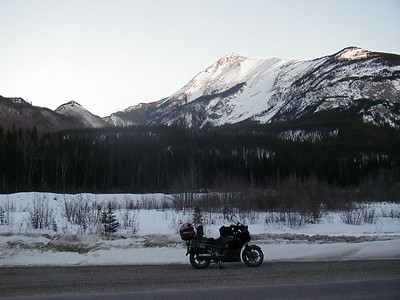 South of Liard Hot Springs, I stop in a roadside pullout to don electrically heated gear and prepare for the cold night ahead as the sun drops over the surrounding mountains.
