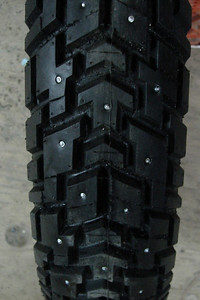 November 2006 - A tire is found to mount on the front of the Wing to go with the rear snow tire, then studded for traction on ice and snowpack.  This is an Avon Gripster with some extra siping cut into it, and studded for traction on ice and snowpack.