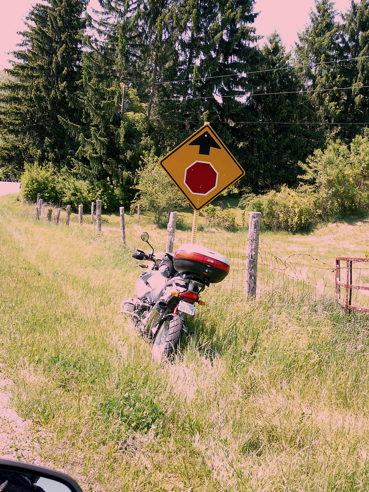 """New BMW side stand, disguised as a """"stop sign ahead"""" sign."""