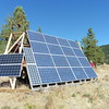 This bank of solar panels charges a large bank of batteries in the shed.  The system provides enough power for a freezer, washer, dryer, dishwasher and lights.  Propane supplements the system with auxiliary heat and gas stove.