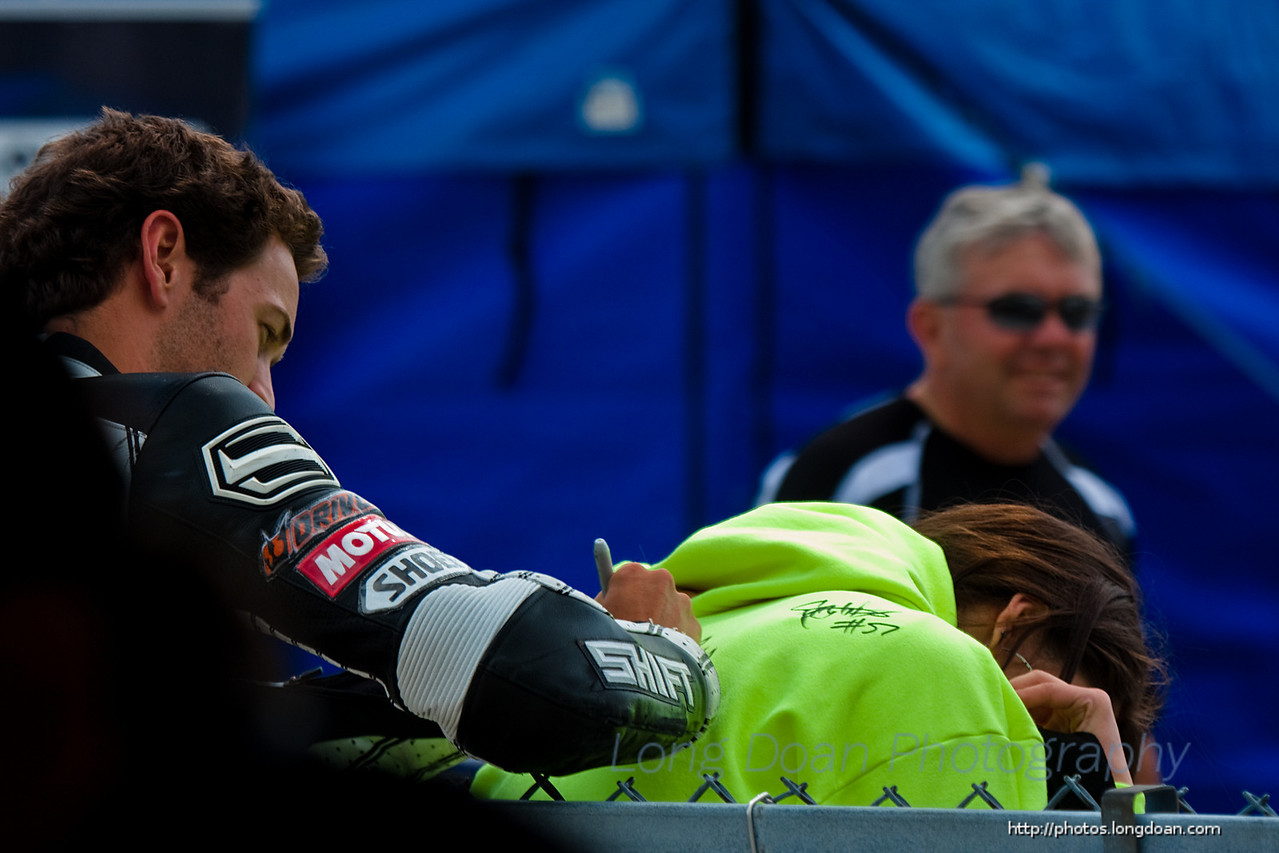 Michael Beck reached over the fence to sign a fan's jacket before the race.