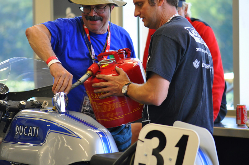 Jim and Rich Lambrechts, gassing up Deja Blue in the Barber museum basement workshop while Cook Neilson waits to ride.