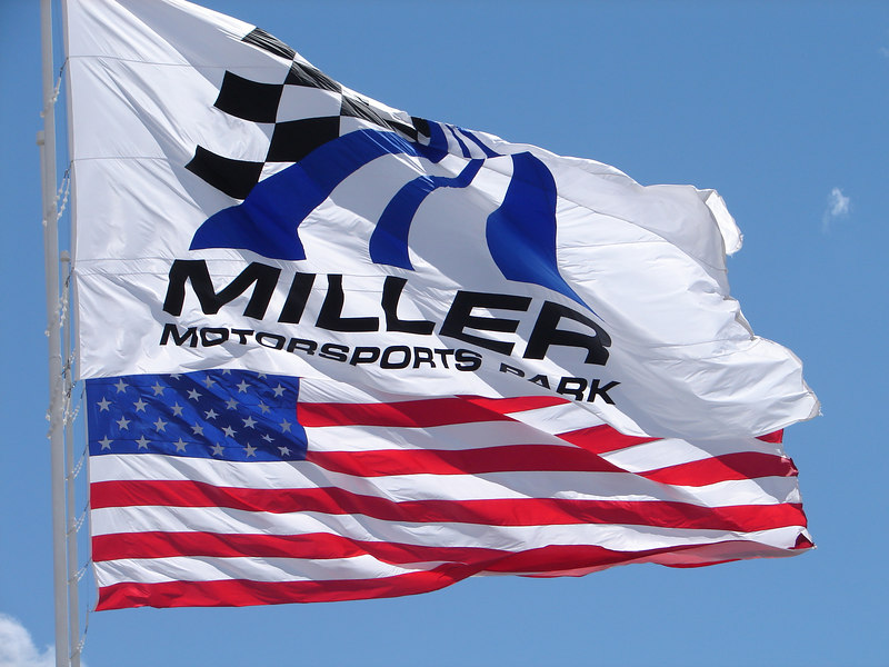 Welcome to Miller! The entrance is flanked by at least 100 flags on poles and the track is surrounded by snow capped mountains and bright blue sky.