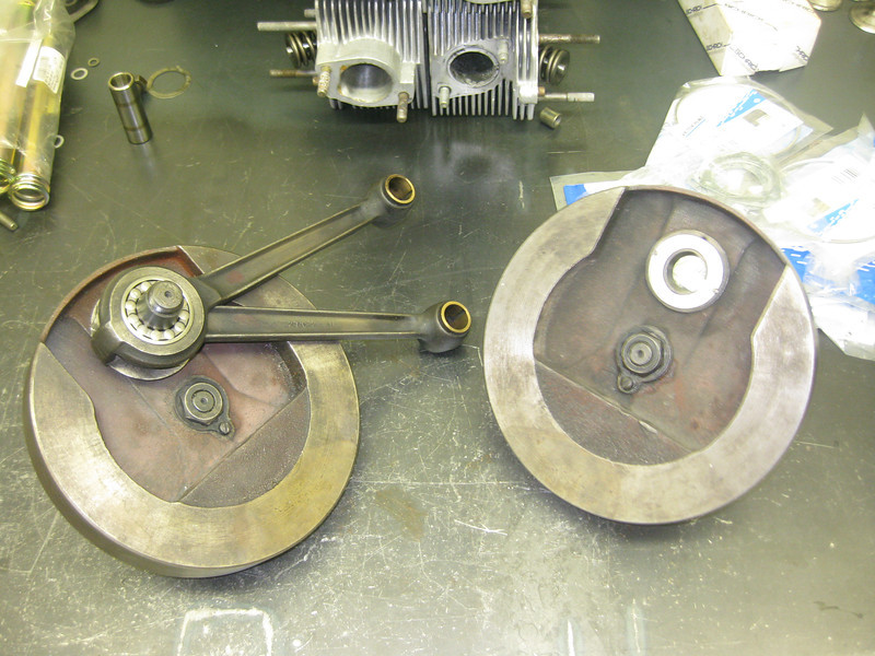 Both pinion, drive shafts and crank pin were perfect but the rod assembly had walked to one side, worn the shim down till there was sufficient clearance for it to rattle of its two pins staking it to the inside of one flywheel.   The excessive .050 clearance contributed to the low whirring sound when this machine was leaned on the side stand.   Repair involved boring for two new pins in the flywheels.   The reason for the rod assembly forced to one siide is that the rollers were assembled with an undersized set on one side of the forked rod causing it to load offset.  It is critical that one size the sets of rollers to the exact same clearance on both races in the forked rod as the inner male rod.