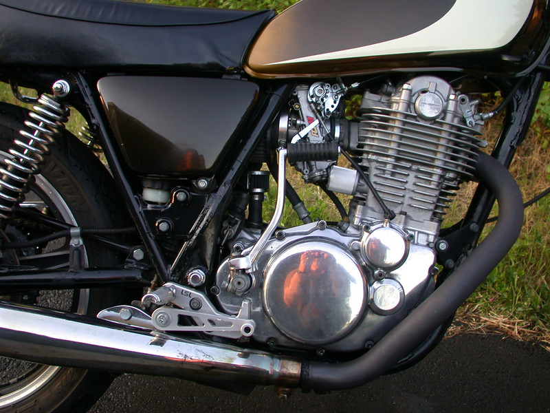 <b>The Motor.</b><br> Arais 10.5:1 piston, MegaCycle street cam, ported and flowed head, 39mm Keihin flatslide pumper carb, Daytona of Japan swept-back header with Performance Coating, authentic BSA Goldstar pipe. Note also...LSL rear sets, billet cam chain tensioner cap.
