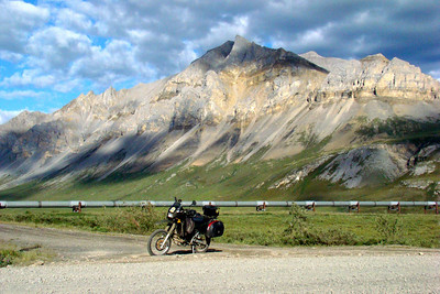 7/4/08 8:10PM - With mountains along the south side of the Atigun River valley as a backdrop, the KLR poses in front of the Trans Alaska Pipeline at Mile 268 of the Dalton Hwy.