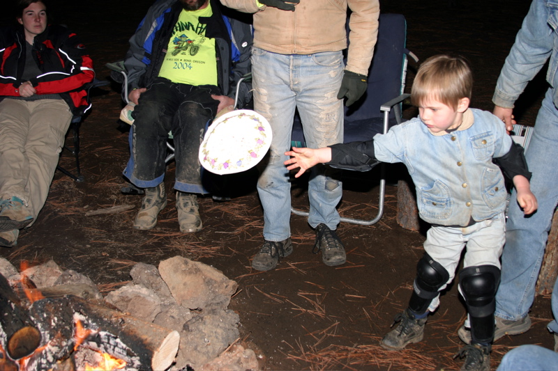 """<font size=""""+3"""">Here's Collin getting a little dangerous while throwing things in the fire..  The fire, incicentally was going 24 hours a day and we figure we burned an easy 1 1/2 cords of wood in four days...  An open fire pit isn't really very efficient.."""