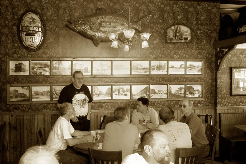 The group gathered at High Noon in the Old Erie Hotel. From L to R: Red Eyes, Tom (standing), Peter's back, Tim Pham, Randy, Richard's back, and Mr. Mott.