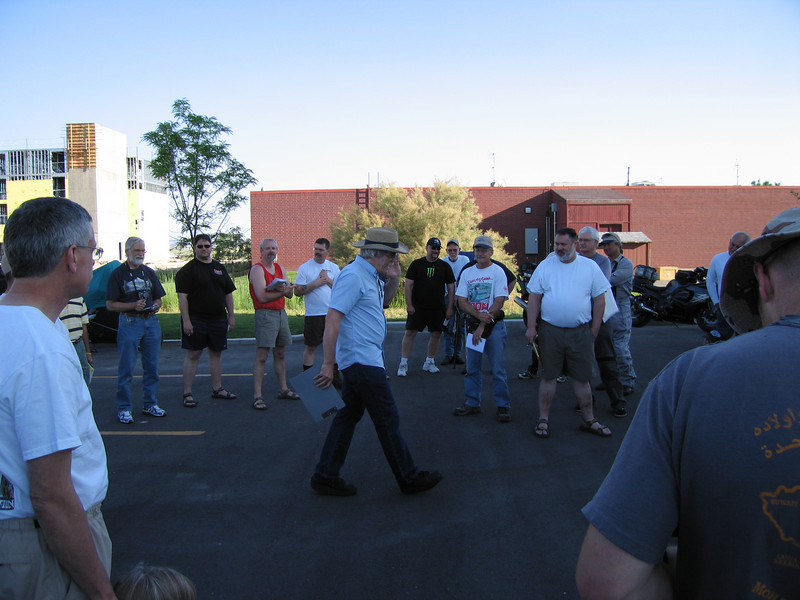 """Steve the Rallymaster, conducting the Friday evening rider's meeting, passing out """"the rock"""""""