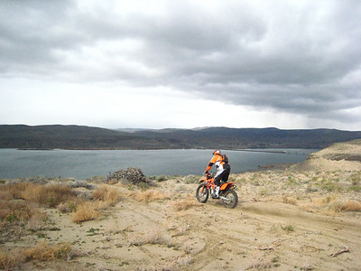 An unknown KTM rider about to over over a steep downhill toward the river.