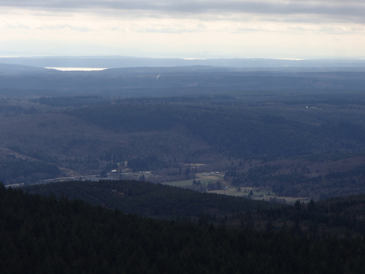 Feb 2014 Looking E from Maynard Hill with E Uncas in the foreground, Hood Canal at the top left, and the Seattle skyline in the haze at top center.