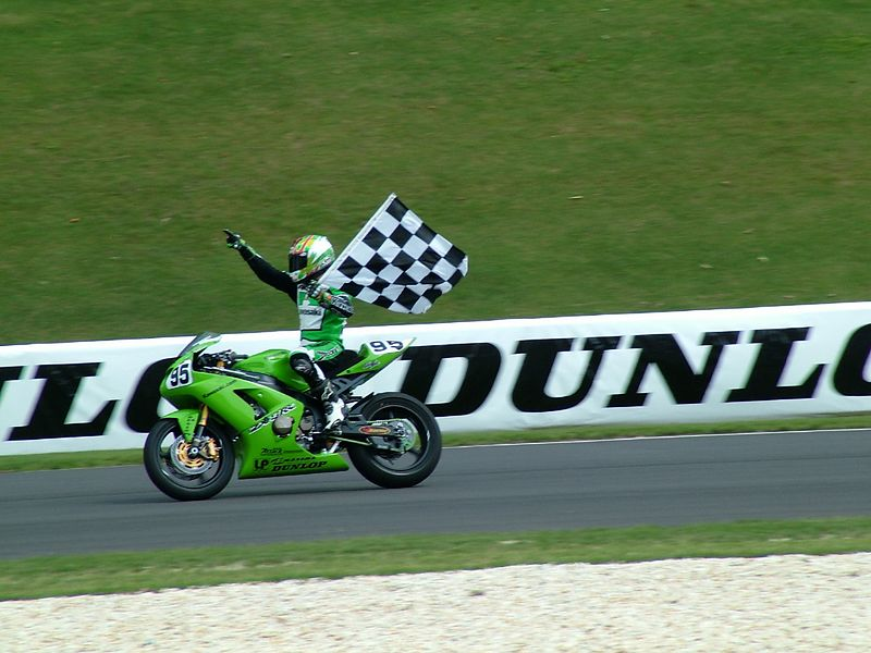 Roger Lee triumphantly displays the checkered flag on the victory lap of first win in the AMA 600 Superbike class.