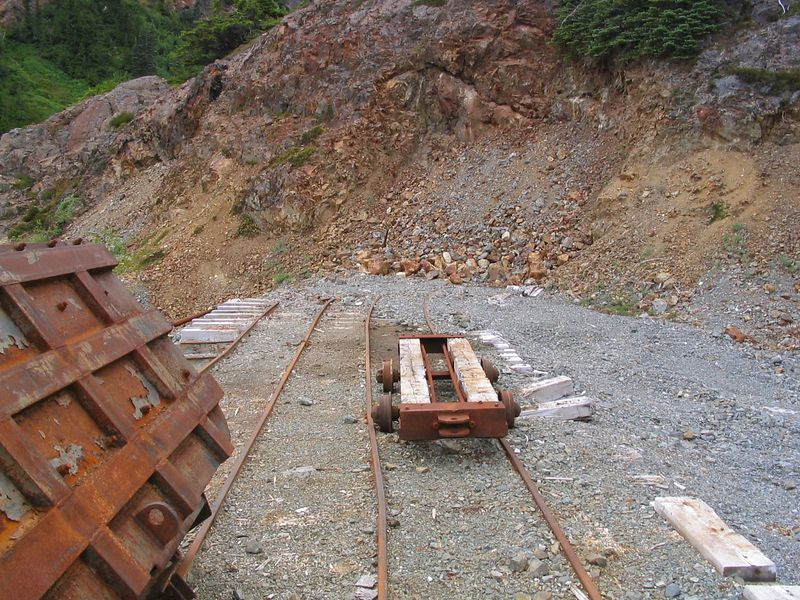 Ore car, rails, and the sealed mine opening straight ahead