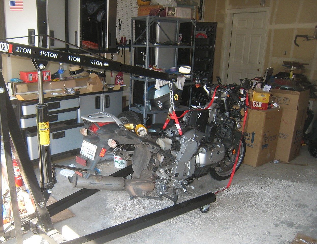 The bike is now supported by the hoist.  The hoist is used to lift the frame off the engine, which provides access to the alternator.  This is almost the pinnacle of the teardown.  After I remove the alternator, I can install the replacement and begin the process of reassembly.
