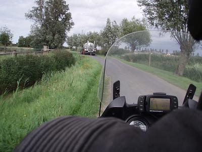 Een boer met tractor en sproeiwagen tussen Sint-Pieters-Kapelle en Slijpe.