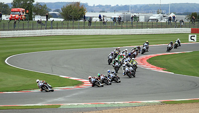 The Triumph Triple Challenge field head through Maggotts Corner and enter Becketts Corner on the first lap.