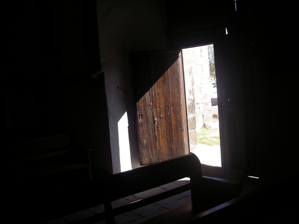 Artsy shot of the old pews and door.