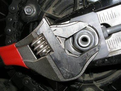 Using a large crescent wrench on the rear axle nut 24mm