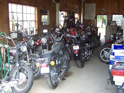"""We were surprised to see the eclectic collection of bikes hiding inside...Cushmans, Triumphs, MZs, etc. That's one of the """"new"""" Royal Enfields in the middle of the photo."""